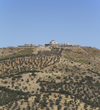 A Fortress in the top of one mountain with many trees Stock Photo