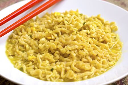 A dish of chicken noodles with red chopsticks Stock Photo