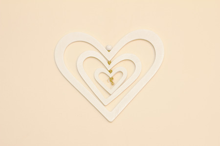 three layer: A three layer white heart made of wood hanging on a cream wall centered in the photo