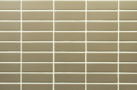 A pattern created with small, real, rectangular, grey ceramic tiles with white clay lines between them