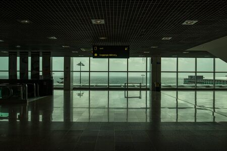 Madeira airport exit completly empty with a great panoramic view to the ocean, in green tone due to the windows glass. Stock Photo