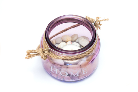 warming therapy: Purple glass pot filled with stones and a candle in the bottom with country feeling home written in it.