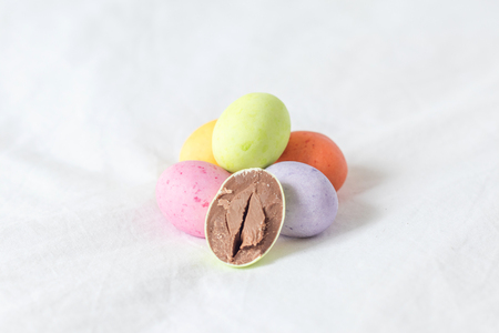 Spring colorful easter eggs sitting in a white sheet with one cutted in half showing it�s milky brown creamy chocolate. Stock Photo