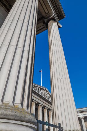 Two enourmous roman stlyled columns agains the clear blue sky and a pole with a united kingdom flag