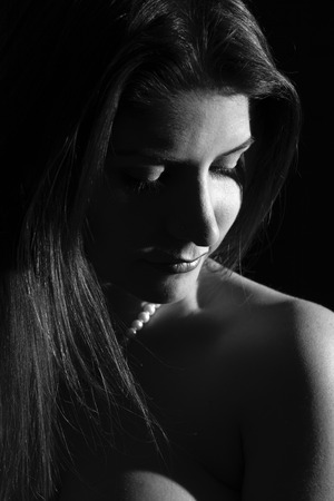 Side portrait in black and white of beautiful brunette woman looking down on her shoulder