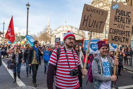 Large group of people walking in the streets of London protesting against cuts and privatisation of NHS