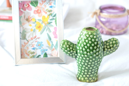 Decorative green vase in form of a cactus plus a aluminium frame with a floral pattern and other decorative ornaments on top of a white sheet.