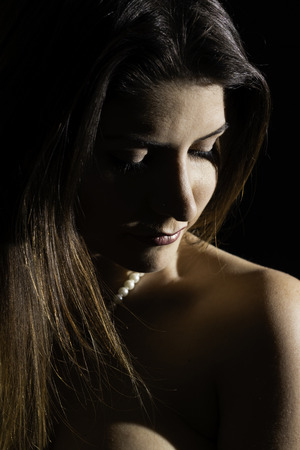 Side portrait in color of beautiful brunette woman looking down on her shoulder