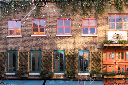 Front view on a building in london full of colorful windows and plants on top and between them