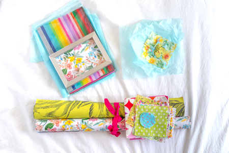 Decorative paper, small pieces of colorful fabric and a frame filled with a floral pattern on top of a white sheet