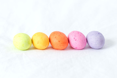 Spring colorful easter eggs sitting in a white sheet all in a horizontal line