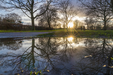 low shot of a couple walking in the park during a cold winter sunset in britain. Stock Photo