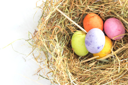 Colorful pastel tone chocolate easter eggs in a nest made of straw in top of a white sheet Stock Photo