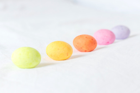 Spring colorful easter eggs sitting in a white sheet forming a diagonal line and white some space between them Stock Photo