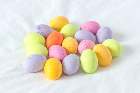 Spring colorful chocolate easter eggs sitting in a white sheet all together in a bunch Stock Photo