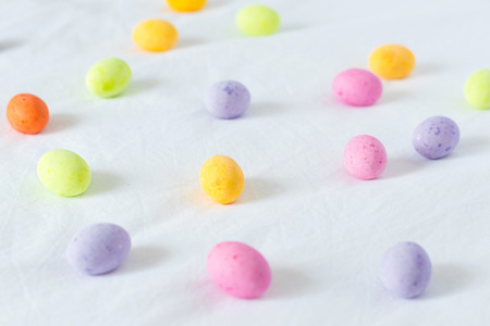 Spring colorful easter eggs scattered around a white sheet Stock Photo
