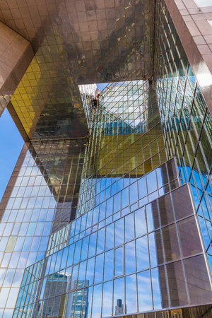 lower view on a skyscraper  with glass facace agains reflecting the clear blue sky and other buildings Stock Photo