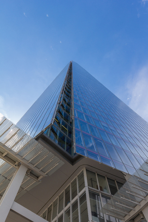 lower view on a skyscraper in form of a pyramid with glass facace agains the clear blue sky Stock Photo