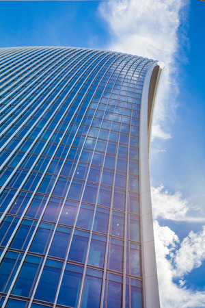 Low view on a skyscraper against the blue sky with curved lines