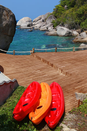 Red canoe at the sea in thailand Tourism bright blue suit Large stones vertical  photo