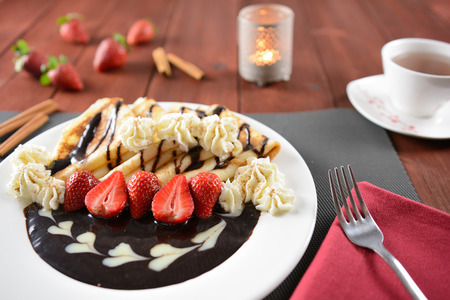 plating: Pancakes with whipped cream, chocolate and strawberries