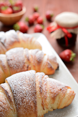 elevenses: Croissants and a strawberry jam on the wooden background