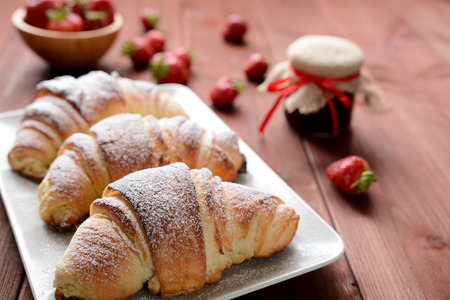 morsel: Croissants and a strawberry jam on the wooden background