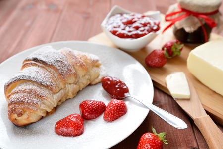 morsel: Croissant and a strawberry jam on the wooden background Stock Photo