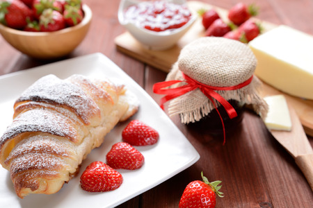 Croissant and a strawberry jam on the wooden background Stock Photo