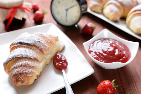 elevenses: Croissant and a strawberry jam on the wooden background Stock Photo