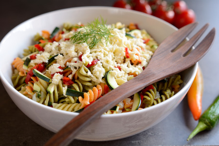 Pasta salad with zucchini, onion, garlic, chili and mozzarella Stock Photo