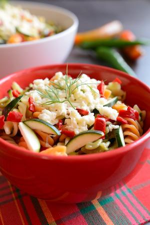Pasta salad with zucchini, onion, garlic, chili and mozzarella Stock Photo