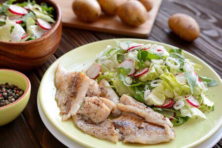 Roasted cod with fresh radish, lettuce and arugula salad Stock Photo