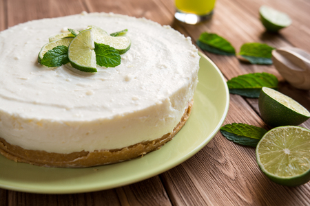 Fresh no-bake cheesecake with lime, mascarpone, whipped cream and mint leaf on a wooden background Stock Photo - 60508611