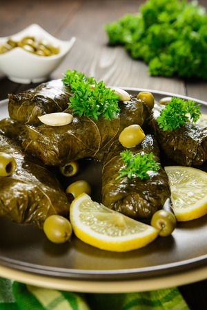 dill and parsley: A plate of traditional Dolma - stuffed grape leaves with rice, onion, dill, parsley, raisins, almonds, garlic and olive oil