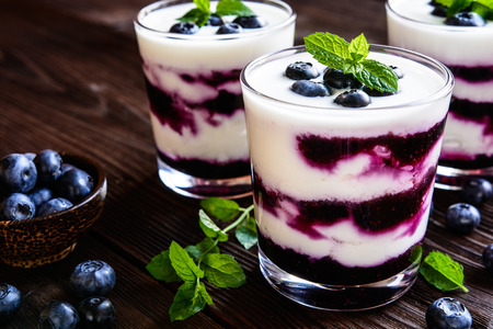 Delicious Greek yogurt with fresh blueberries in a glass jar on a wooden background