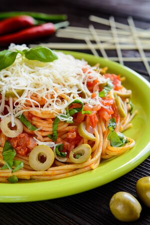 marinara sauce: Spaghetti pasta salad with tomato sauce, olives, Gouda cheese and basil on a wooden background