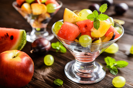 sliced watermelon: Fresh juicy fruit salad with watermelon, plums, nectarines and grape in a glass jar on a wooden background Stock Photo
