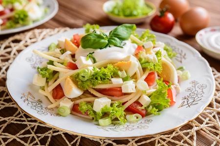 スパゲッティ パスタ トマト、レタス、卵、フェタチーズ、青ネギ、バジルと木製の背景にサワー クリーム ドレッシング