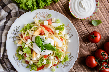 quick snack: Spaghetti pasta with tomato, lettuce, egg, Feta cheese, green onion, basil and sour cream dressing on a wooden background