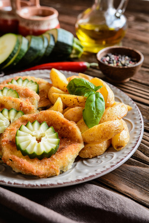 jacked: Breaded fried zucchini slices with American potatoes and cucumber on a wooden background Stock Photo