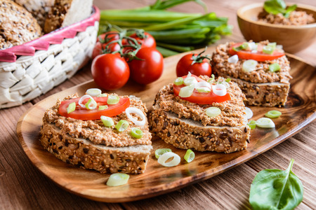 Whole wheat bread slices with sardine spread, tomato and green onion on a wooden background