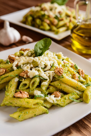 olive green: Penne pasta with spinach pesto sauce, walnuts and mozzarella on a wooden background Stock Photo