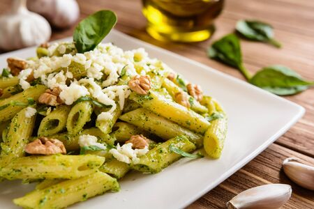 quick snack: Penne pasta with spinach pesto sauce, walnuts and mozzarella on a wooden background Stock Photo