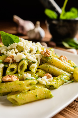 Penne pasta with spinach pesto sauce, walnuts and mozzarella on a wooden background Stock Photo