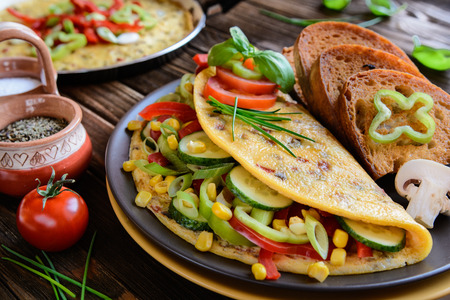 quick snack: Omelet with pepper, tomato, corn, green onion, cucumber, mushrooms and fried bread on a wooden background Stock Photo