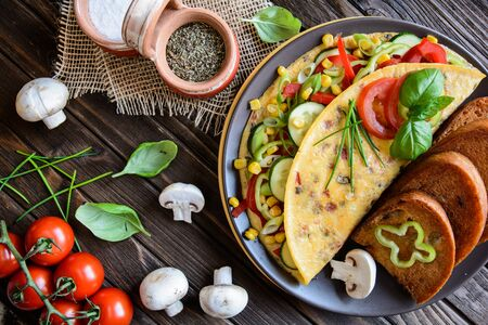 Omelet with pepper, tomato, corn, green onion, cucumber, mushrooms and fried bread on a wooden background Stock Photo