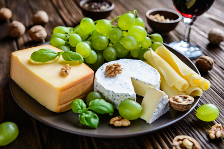 edam: Assorted cheese - smoked gouda, camembert, edam slices with grape, walnuts and red vine