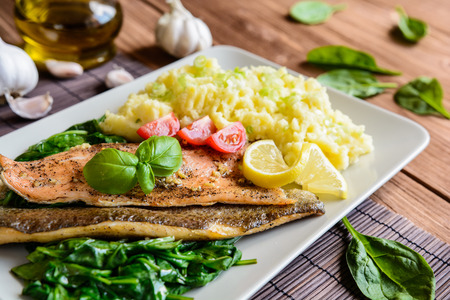 Baked rainbow trout fish with mashed potatoes and steamed spinach Stock Photo