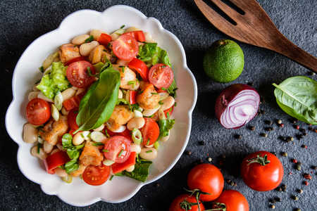 vitamin rich: Vegetable salad with white beans, fried fish pieces, red pepper, green onion and chive Stock Photo